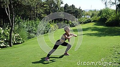 Молодая женщина сидеть на корточках работая, протягивать и тренировка outdoors Здоровый, фитнес, образ жизни здоровья Спорт, card акции видеоматериалы