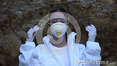 Молодая женщина снимает защитную маску, свободно дыша в лесу, меняет климат видеоматериал