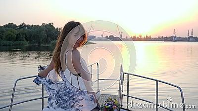 Молодая женщина стоит на смычке парусника на заходе солнца предпосылки в перемещении лета сток-видео