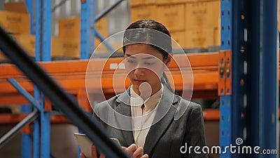 Молодая коммерсантка используя цифровую таблетку проверяя запас в промышленном складе