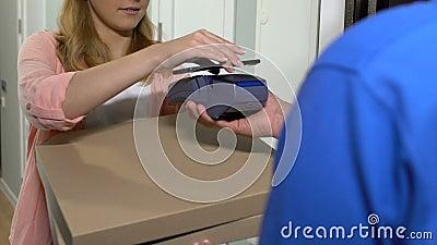 Молодая красивая женщина принимает доставку пиццы и платит с помощью мобильного приложения видеоматериал