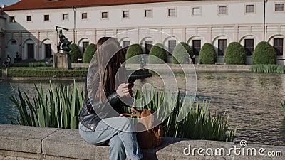 Молодая привлекательная девушка, использующая смартфон, сидя в красивом парке у пруда есть дворец валленштейна и акции видеоматериалы