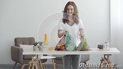 Молодая улыбающаяся женщина кладет сумки с фруктами и овощами на стол в современном офисе Понятие здорового питания видеоматериал