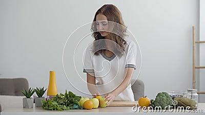 Молодая умница ставит яблоки на стол, стоя на современной кухне Понятие здорового питания Профессия акции видеоматериалы