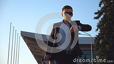 Молодой бизнесмен в официально черном костюме смотря его вахту и быстро идя с его багажом Красивый человек внутри сток-видео