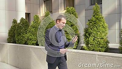 Молодой бизнесмен идя вниз по улице и агрессивно водит обсуждение на видео- звонке сток-видео