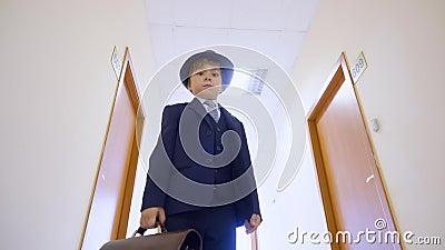 Молодой мальчик в деловом костюме, положение шляпы в коридоре школы и смотреть к камере Бизнесмен взгляда низкого угла молодой с акции видеоматериалы