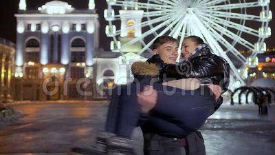 Молодой парень завихряет его подругу на оружиях на предпосылке колеса ferris ночи акции видеоматериалы