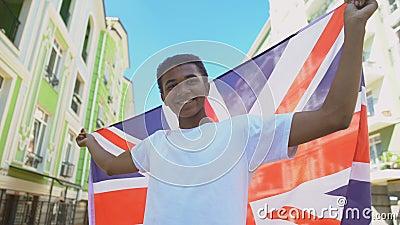 Молодой парень из смешанной расы, размахивающий британским флагом и улыбающийся, национальный праздник сток-видео