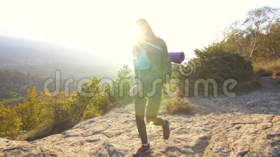 Молодой турист с рюкзаком взбирается гора и поднимается ее руки вверх с утехой сток-видео