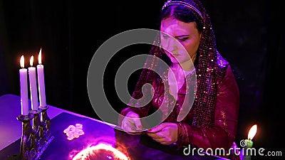 Молодой цыган освобождает карты перед удач-говорить над волшебным огненным шаром сток-видео