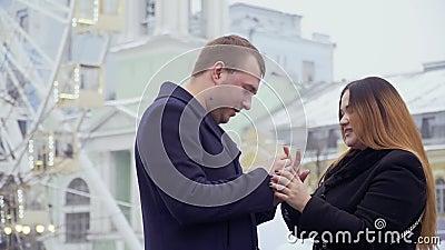 Молодой человек делает предложение руки и сердца к красивой женщине в парке атракционов видеоматериал
