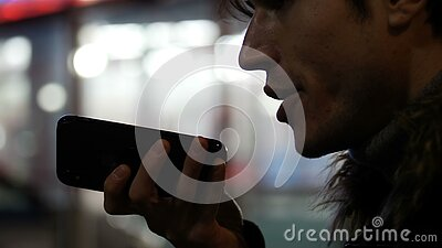 Молодой человек посылая сообщение голоса с сотовым телефоном видеоматериал