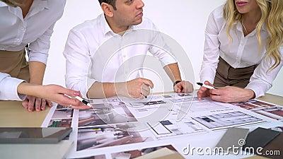 Молодые архитекторы, построители, или люди дизайнеров над гостиной выбирают цвет для интерьера творческо видеоматериал