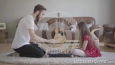 Молодые бородатые отец и маленькая девочка с длинными волосами играя шахматы сидя на поле на пушистом ковре перед сток-видео