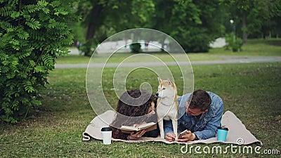 Молодые выходные траты семьи в парке, книга чтения женщины, человек используя smartphone, милую собаку отдыхая между ими ванта видеоматериал