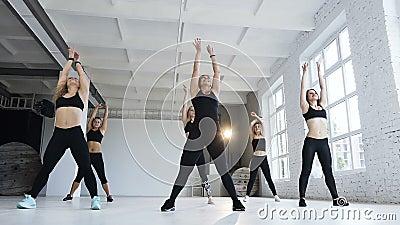 Молодые люди в черных bodysuits, работая в классе фитнеса в ярком фитнес-центре, соответствующие красивейшие женщины сток-видео