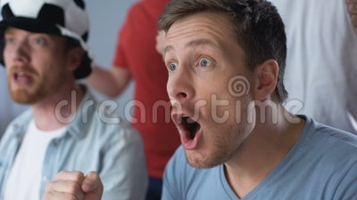 Молодые человеки смотря футбольную игру на ТВ, крупном плане рожка вентилятора сторонника дуя сток-видео