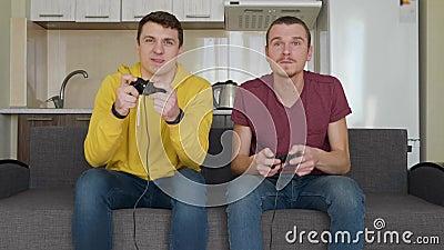 2 молодых парня играя видеоигру дома на кресле на фоне кухни акции видеоматериалы