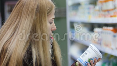 Молокозавод молодой женщины покупая или refrigerated бакалеи на супермаркете в refrigerated разделе видеоматериал