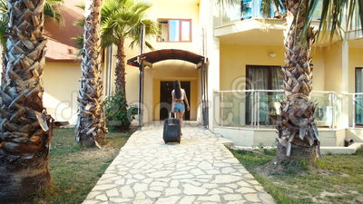 Молодая женщина брюнет в шортах и пятках приходит с чемоданом между пальмами в гостинице в лете Праздник и каникулы акции видеоматериалы