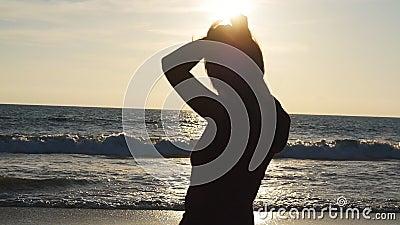 Молодая женщина брюнет связывая ponytail на пляже около моря на заходе солнца Красивая девушка сжимает ее волосы на береге океана сток-видео