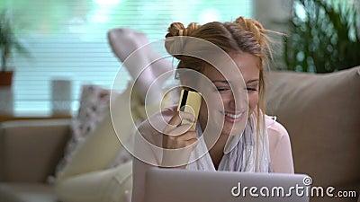 Молодая женщина использует лежать золотой кредитной карточки онлайн на кресле Съемка тележки видеоматериал