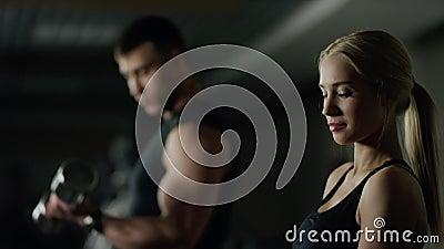 Молодая женщина и человек делая разминку фитнеса с гантелями
