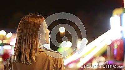 Молодая женщина смотря carousel в парке атракционов акции видеоматериалы