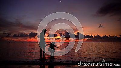Молодая женщина с маленькой девочкой на пляже на заходе солнца сток-видео