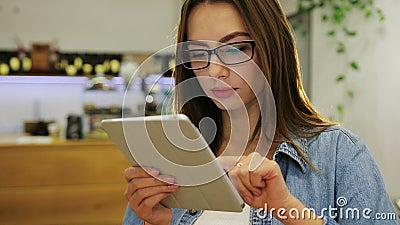 Молодая привлекательная женщина используя экран касания таблетки и в современном кафе акции видеоматериалы