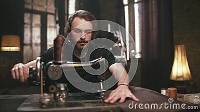 Молодой, бородатый человек, делает кожаные товары