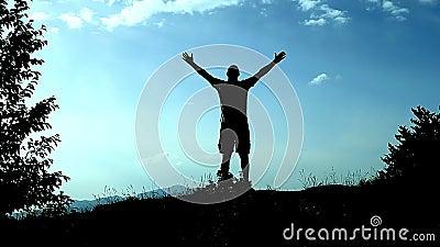 Молодой человек силуэта бежит до верхней части горы и воздевает его руки как знак достижения, успеха и утехи Концепция акции видеоматериалы
