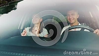 Молодые пары имея потеху в автомобиле Потеха, поет и танцует Лобовое стекло отражает деревья и облака управляя автомобилем видеоматериал