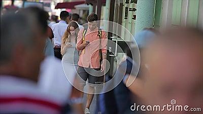 Молодые пары идут вдоль занятой улицы города и смотрят их smartphones в замедленном движении сток-видео