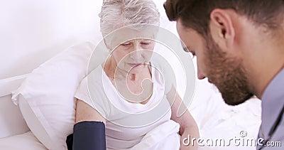 Мужская медсестра измеряя кровопролитное давление к старшей женщине видеоматериал