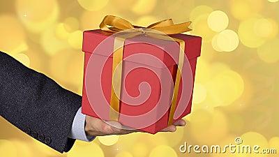 Мужская рука человека держит красную подарочную коробку с смычком золота Отпразднуйте подарочную коробку кануна присутствующую Ка видеоматериал