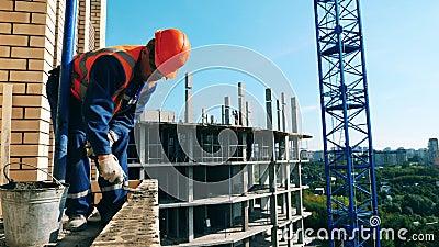 Мужской конструктор распространяет цемент вдоль кирпичей акции видеоматериалы