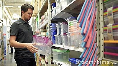 Мужской клиент в магазине Он принимая пластмасовый контейнер от полки акции видеоматериалы