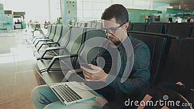Мужской пассажир сидя в ждать зале в авиапорте и отправляя СМС sms smartphone видеоматериал