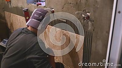 Мужской работник проверяя стену с уровнем на новой квартире сток-видео