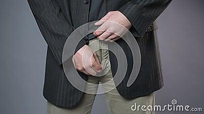 Мужчина в черной куртке вытягивая его брюки застегивает на молнию, замешательство, здоровье человека сток-видео