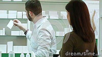 Мужчина-фармацевт и женщина-клиент в аптеке сток-видео