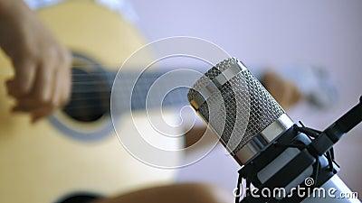 Музыкант, играющий на гитаре, записывает в студии звукового смешивания процесс создания музыки с темно-зерновой обработкой видеоматериал