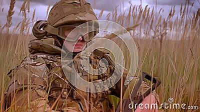 Настойчивый подлинный кавказский солдат в сидеть шлема и камуфлирования нося в высоком изолированном degrasse и смотреть акции видеоматериалы