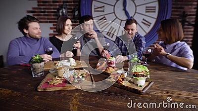 На деревянном столе в ресторане много вегетарианские закуски, на заднем плане компания друзей видеоматериал
