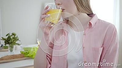 Неузнаваемая миленькая девушка, пьющая апельсиновый сок и улыбающаяся перед камерой Молодая кавказка наслаждается вкусной органик акции видеоматериалы