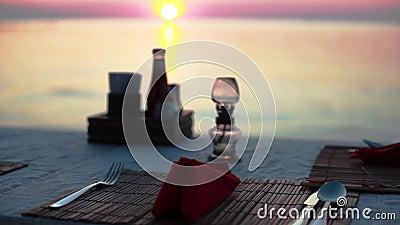 обедать пляжа Vew таблицы с столовым прибором на пляжном ресторане во время захода солнца видом на море 1920x1080 видеоматериал