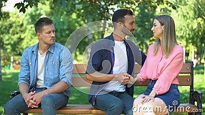 Одинокий мужчина сидит на скамейке в парке и смотрит романтические чувства влюбленной пары сток-видео