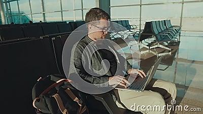 Один мужской пассажир ждет его полет в стержень и просматривает в компьтер-книжке сток-видео